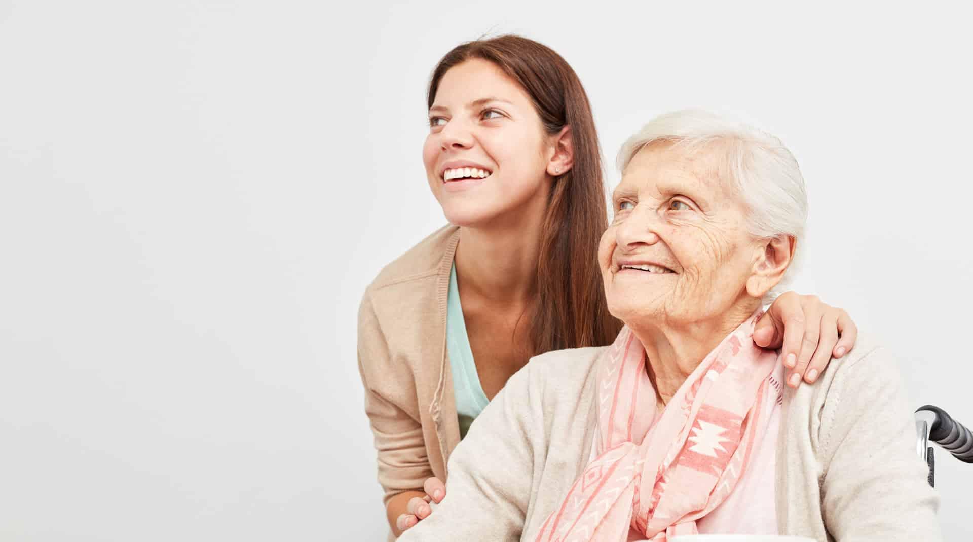 Betreuerin und Seniorin schauen lächelnd in die Zukunft